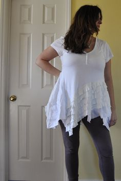 This a teeshirt top tunic dress for a plus size XL XXL size woman. The hem is tattered and uneven and flirty. There are groves and puckers raw and threadbare extras in this white Aline patched up ruffled uneven hem top. The top is made for layer under and over year round basic funky quirky go to piece for the art to wear gypsy heart.  Model in image is size 16/18 and wears XXL 1x and 2x items, tall 5 10 plus size woman. She is currently wearing a basic aline tank top tunic underneath the...