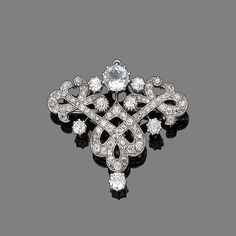 An aquamarine & diamond Belle Epoque brooch/pendant, c1910 with later rhodium plating. The scroll cartouche is set with old brilliant-cut diamonds & a circular-cut aquamarine. Approx 3.0ct diamonds. Pinned by #Blucha from bonhams.com