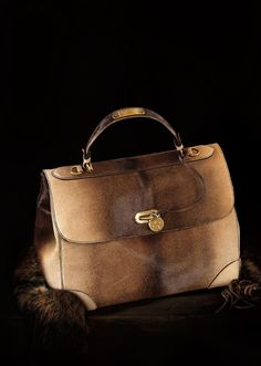 This Italian-made haircalf satchel strikes the perfect balance between classic and modern with a structured silhouette and an ombré pattern. Embellished with polished gold-toned hardware, including a turn-lock closure, it exudes rustic elegance and is outfitted with a removable shoulder strap for versatile wear.
