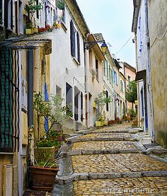 A quaint picturesque cobblestone street winds up a hill, with pots of bright flowers in pots, and colorful painted homes in Arles, in Provence, in the south of France, a city classified as as Unesco World Heritage site.