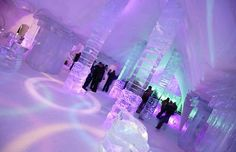 The Hotel de Glace's gabled in Quebec, igloo-esque exterior leads to whimsically carved rooms below with colorful lighting that takes advantage of transparent and reflective walls.