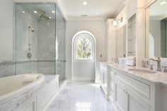 I love the arched window in this elegant bathroom.