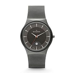 Skagen Grey & Black Titanium Watch.  Modern design comes alive with the fusion of a titanium case housing carbon fiber elements in the dial and top ring. This model comes in a matte titanium case with grey carbon fiber lower dial and top ring brought together with a heavy gauge charcoal mesh band.