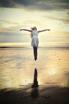 A girl jumping feet down in the water with her arms open. It's beautiful. Majestic.