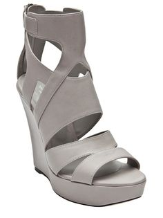 Tiger banded wedge in grey from Tania Spinelli. These leather strappy wedges feature an open toe, strappy upper with cut-outs, and back zipper closure. Platform measures 1