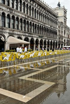 yellow cafe chairs during aqua alta in Piazza San Marco, Venice, Italy.