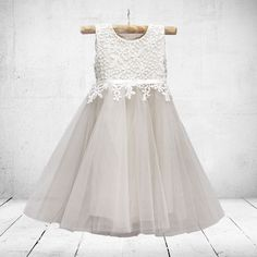 A dress made with layers of tulle and lace. The inner body of the dress is made from a stretchy viscose material.  The dress is made sleeveless by…
