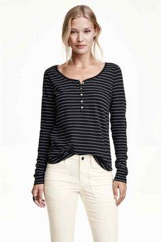 Koszulka z długim rękawem: CONSCIOUS. Koszulka z długim rękawem z miękkiego dżerseju zawierającego ekologiczną bawełnę. Nieco szerszy dekolt i guziki u góry. Lekko zaokrąglony dół.