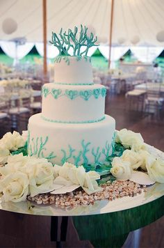 The three-tier wedding cake is decorated with turquoise swags and topped with sugar coral.