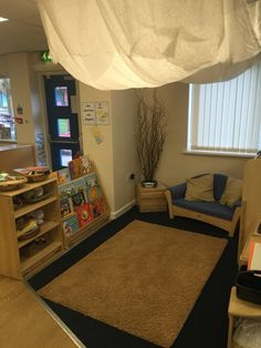 Cosy gathering / story area with story boxes including props. The drape on the ceiling is held up using wooden sticks collected from the garden.
