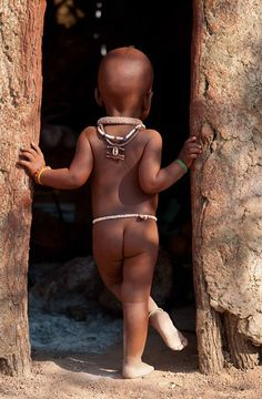 Africa | Little Himba boy standing in the doorway of a traditional home.  Near Kamanjab, Namibia | ©Adam Lees