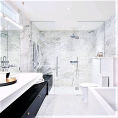 Quarried in Italy, the snowy white base of Bianco Gioia is strewn with complex grey veining that echoes the patterns of a masterful abstract painting. It makes the perfect sophisticated statement in this gorgeous bathroom designed by Astro Design Centre 🤍  📷: JVL Photography White Marble Bathrooms, Bathroom Gallery, Bathtub, Modern, Centre, Italy, Patterns, Design, Abstract