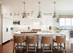 Richard Bubnowski Design    Lovely kitchen with white kitchen cabinets with granite countertops, sink in curved kitchen island, woven seagrass counter stools, Restoration Hardware Benson Pendants, subway tiles backsplash, gray walls paint color, wood panel fridge and wine fridge.
