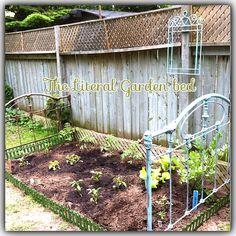 Veggie garden- old iron frame serves as trellis. Adorable :)