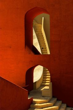 Architectural Line: thick tomato red walls and the grace of a curving staircase