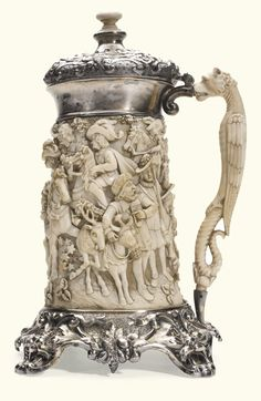A SILVER-GILT AND IVORY TANKARD, GERMAN, CIRCA 1880 carved with a a hunting scene in Troubadour style, the handle formed as a mythological beast, ivory button finial, the silver-gilt lid and base embossed and engraved with masks and fruits, later Dutch import mark 30.5cm., 12 in high
