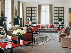 Living room with brilliant red accents and hide rug designed by @Suzanne Lovell, Inc.