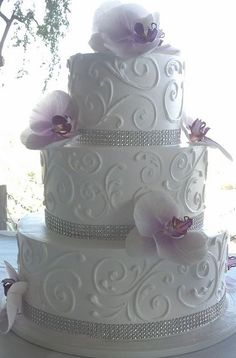 White wedding cake with lavender orchids and crystals.