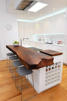 The island top became the center piece of the kitchen. A solid slab of locally harvested walnut, cantilevering off the island, serves as a massive bar top. Sourced from Arborica, in Marshal California, the clients hand picked the slab with the guidance of owner/sawyer Evan Shively, from his famed 'Jewelry Box'. The natural edges of the walnut provides a striking contrast to the highly refined polished cabinetry and cesar stone countertops.