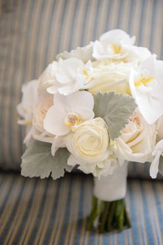 Carry a romantic, airy bouquet filled with phalaenopsis orchids, garden roses, ranunculuses, and dusty miller.