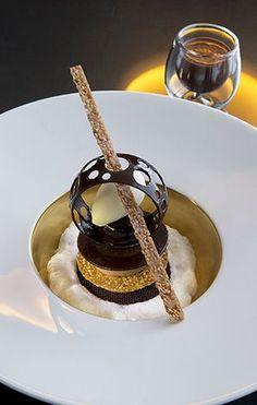 Una original milhojas de chocolate y frutos secos, con elaborada filigrana también de chocolate.