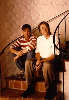 Steve Jobs and Bill Gates sitting on steps, color photography, Steve in red white striped shirt,