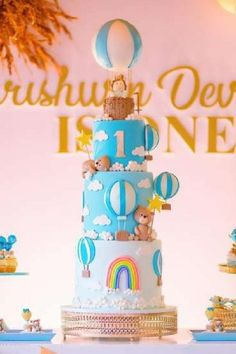Check out the impressive tiered birthday cake decorated with hot air balloons, clouds, and a beautiful rainbow at this Hot Air Balloon 1st birthday party! See more party ideas and share yours at CatchMyParty.com