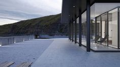 defined by tones of grey and blue, the 'FH1 house' provides warmth   safety at the edge of the ocean.