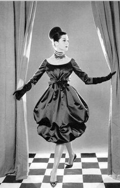 Model in ruby red satin dress with double-bubble skirt, high narrow belt knotted just above the waist, worn with chignon-cap, by (Yves Saint Laurent) Christian Dior