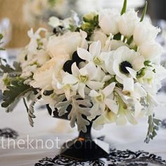 Black footed vases held French anemones, tulips, dendrobium orchids, cymbidium orchids, japhet orchids, and accenting black Billy balls, seasonal foliage, and dusty miller
