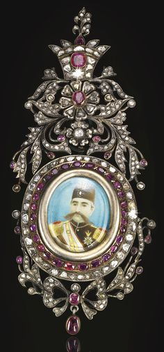 A RARE GEM-SET SILVER INSIGNIA OF THE ORDER OF THE IMPERIAL EFFIGY DEPICTING MUZAFFAR AL-DIN SHAH QAJAR (R.1896-1907), PERSIA, CIRCA 1900 featuring an oval painted portrait of Muzaffar al-Din Shah Qajar within a thick silver mount set with rubies and diamonds, with flowerheads and leafy sprays topped by a crown above and bow-tie underneath with hanging rubies, the reverse with suspension clip