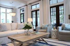 Living room furniture, rug and chairs. Beuatiful slipcovered sofa and whitewashed coffee table are from Beau Interiors in Grayton Beach, Florida. #livingroom #furniture Old Seagrove Homes.