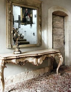 Stone floor, hall table, mirror, arch... it's all beautiful.