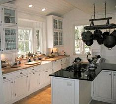 white kitchen with black stone top island that contains a cooktop