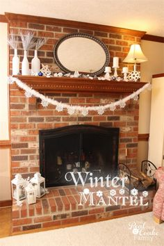 Pretty winter mantel home decor using glitter snowflakes, wine bottles, candles and hurricane lamps.