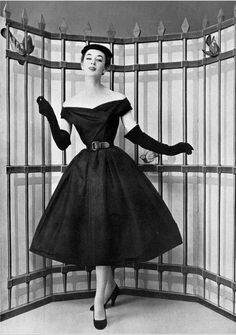 1954 Elinor in charming black faille dinnercocktail dress, full skirt, off-shoulder bateau neckline, cinched at waist with black leather belt, by Christian Dior