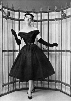 1954 Elinor in black faille dinner cocktail dress, full skirt, off-shoulder bateau neckline, cinched at waist with black leather belt, by Christian Dior