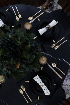 a moody winter setting with black plates, gold goblets, evergreens and black candles