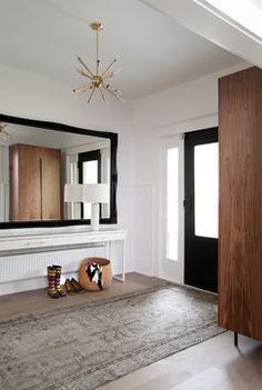 Love the dramatic appeal of this oversized framed mirror in the entryway of this Edwardian home!