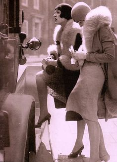 Two well dressed flappers iin short skirts & heels,  helmet style cloche hats & fur trimmed coats, alight from a taxi at a polling station  in May 1929 to vote in the U.K General Election From Retro Fashion by Lucinda Gosling (2015) (please follow minkshmink on pinterest) #flappers #twenties