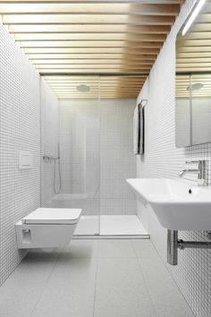 White mosaic tile walls, white tile floors, wood ceilings, white fixtures, minimalist