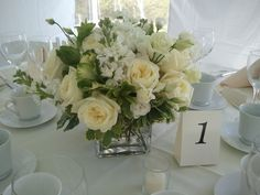 Green and white centerpieces featured garden roses, hydrangea, kale, stock and lisianthus in square, cube vase