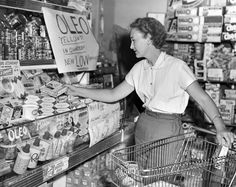 "Mrs. Bryce Miller purchases yellow oleo margarine in Hamburg, Iowa, in this World-Herald photo taken July 6, 1953. Newly passed legislation removed tax restrictions on oleo sold in Iowa and permitted stores to sell it with a yellow color. Before the law, grocers in Hamburg had to compete with Nebraska and Missouri stores, where customers could buy colored margarine. ""I've always used oleo,"" Miller said, ""and now I think it's wonderful that I can buy it — like I want it — right here in Hambur..."