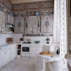 So much pop with so little color... Kitchen of the Paris flat of Dimonah and Mehmet Iksel, featured in Elle Decor. Indian pattern painted on cabinets.
