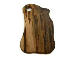 This maple serving board is made out of a solid piece of ambrosia maple. It has a unique shape with a hole at the top for a handle. The grain has some very nice ambrosia streaks of light and dark coloring. This one of kind board can be used as a food serving board or cutting
