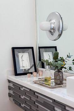 O lavabo tem bancada com detalhes de madeira acinzentada e arandela. O projeto leva a assinatura dos arquitetos Carla Mattioli e Maurício Pinheiro Lima