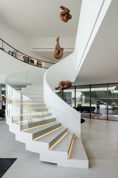 A curved white staircase with glass handrails and hidden lighting connects the various levels of this modern house. The Fraiao House by TRAMA Arquitetos Ka Ny mobnyka stairs A curved white staircase wi Glass Stairs Design, Home Stairs Design, Interior Stairs, Modern House Design, Stair Design, Spiral Stairs Design, Glass House Design, White Staircase, Curved Staircase