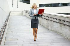 A young blond is walking outdoors with a laptop