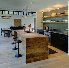 The kitchen's island is clad in reclaimed pine, the counter tops are lava stone, the lower matte black cabinets are Ikea, the kitchen handles are leather straps, and the shelves are raw beams.