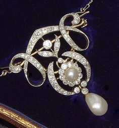 A late 19th century pearl and diamond brooch/pendant.  Of scrolling openwork…